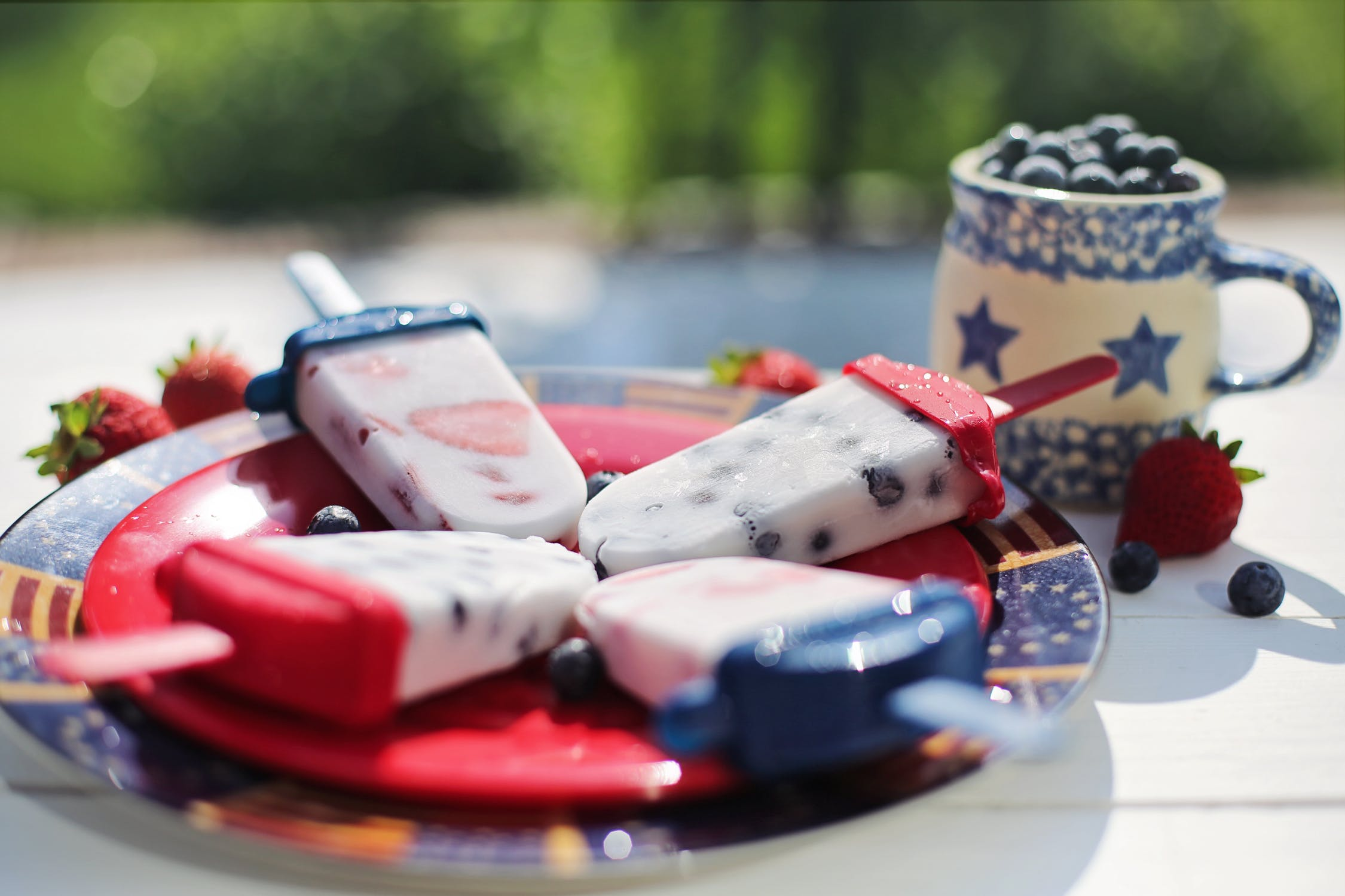 Patriotic colored frozen fruit bars on a plate beside fresh cup of blue berries and scattered strawberries