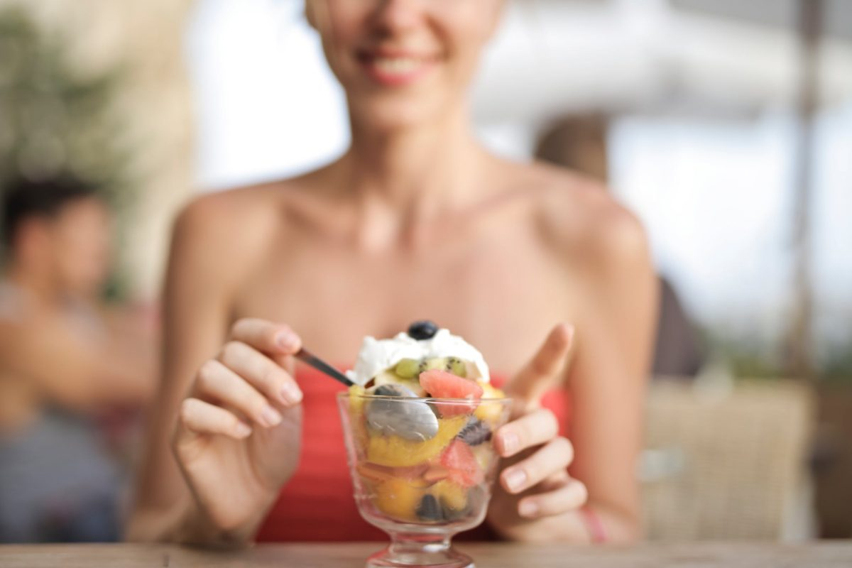 happy girl with ice cream and fruit in a glass cup